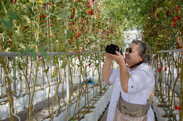 Mulher adulta que toma a foto na jardinagem. prolongar a mulher de aposentadoria ativa para fazer atividades