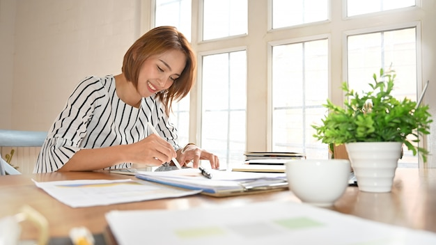 Mulher adulta que trabalha com tabuleta e pena digitais.