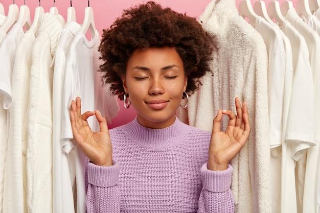 Mulher adulta relaxada, de pele escura, faz gesto de paz, usa suéter de tricô roxo e fica perto de roupas brancas selecionadas em cabides