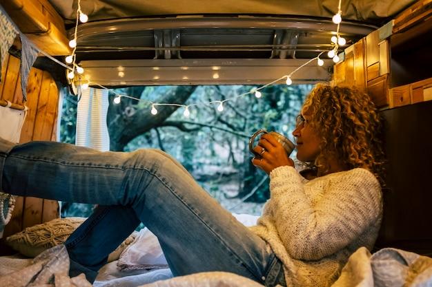 Mulher adulta relaxada dentro de uma van de madeira vintage curtindo a natureza