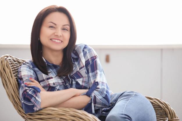 Mulher adulta, relaxando em casa, posando na cadeira
