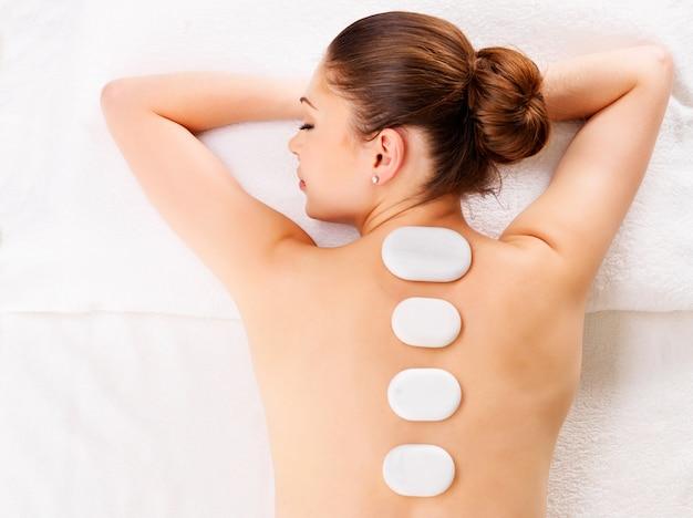 Mulher adulta relaxando em um salão de spa fazendo terapia com pedras quentes na coluna vertebral