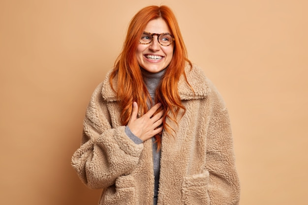 Mulher adulta ruiva radiante ri e expressa emoções sinceras e felizes usa óculos e um casaco de pele marrom quente concentrado ao lado com um sorriso no inverno tem um clima otimista. conceito de moda