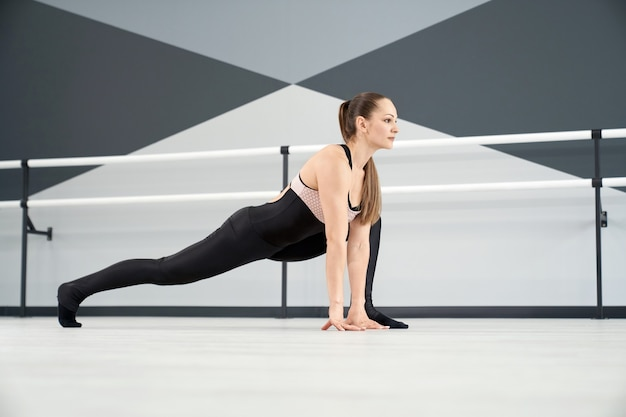 Mulher adulta se alongando em estúdio de balé