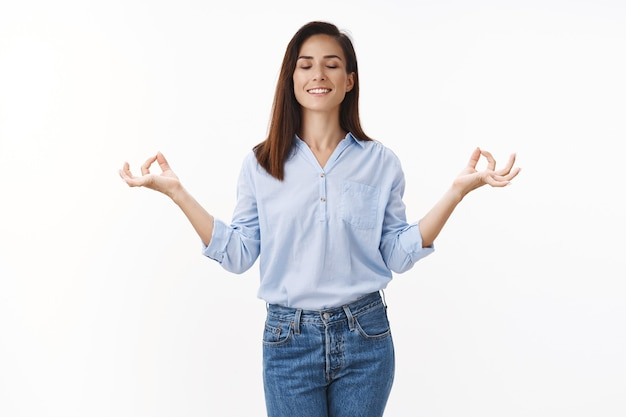 Mulher adulta se sente aliviada, sem estresse, respira, inala o ar, sorrindo alegremente, postura de meditação de lótus de olhos fechados, prática de ioga calma, exercício de respiração, parede branca paciente de pé