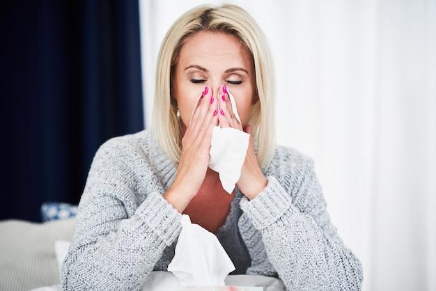 Mulher adulta se sentindo mal e com gripe em casa