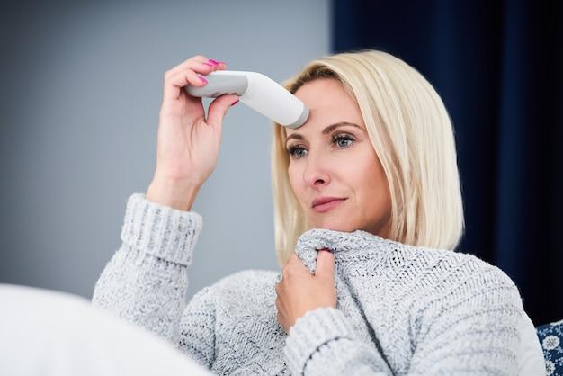 Mulher adulta se sentindo mal e verificando a temperatura em casa