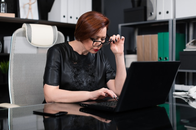 Mulher adulta, segurando os óculos de mão e olhando através deles no monitor no escritório