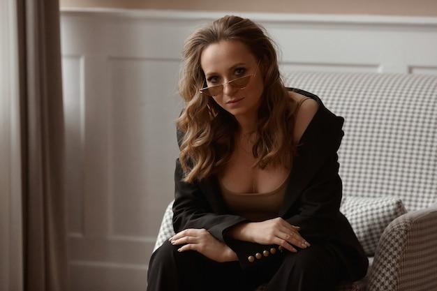 Mulher adulta sem maquiagem, usando óculos escuros da moda, posando em um interior clássico
