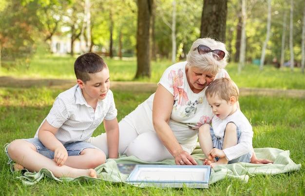 Mulher adulta sênior e meninos jogando jogo de tabuleiro do lado de fora