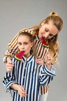 Mulher adulta sorridente e de cabelos compridos propondo seu doce de açúcar para a irmã mais nova enquanto come seu doce