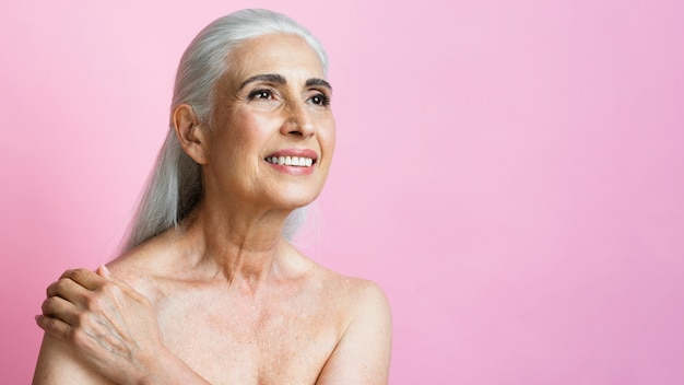 Mulher adulta sorrindo em fundo rosa
