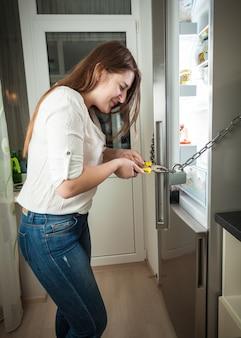 Mulher adulta tentando cortar a corrente na geladeira com um alicate
