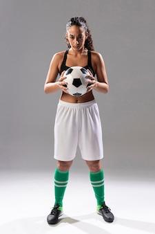 Mulher adulta tiro cheio, segurando bola de futebol