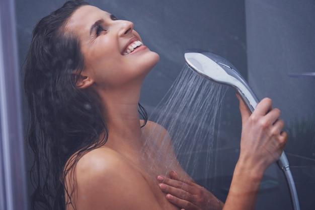 Mulher adulta tomando banho no banheiro