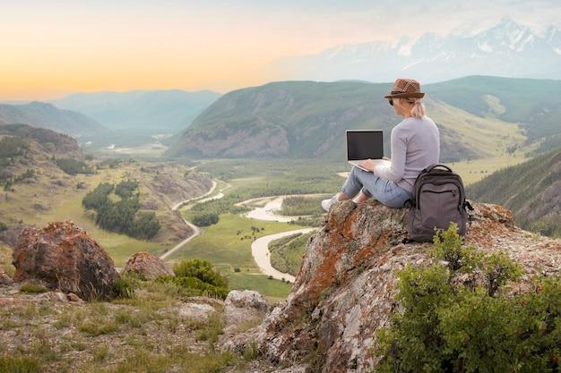 Mulher adulta trabalhando em seu computador no topo da montanha ao pôr do sol. conceito de trabalho remoto.