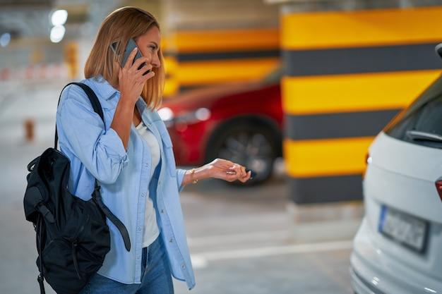 Mulher adulta usando celular em estacionamento subterrâneo