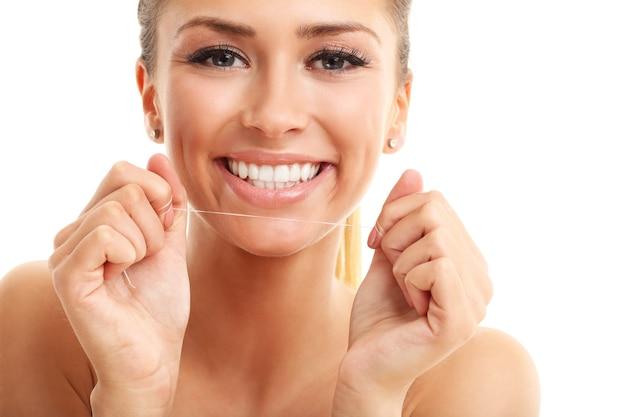 Mulher adulta usando fio dental isolado no branco