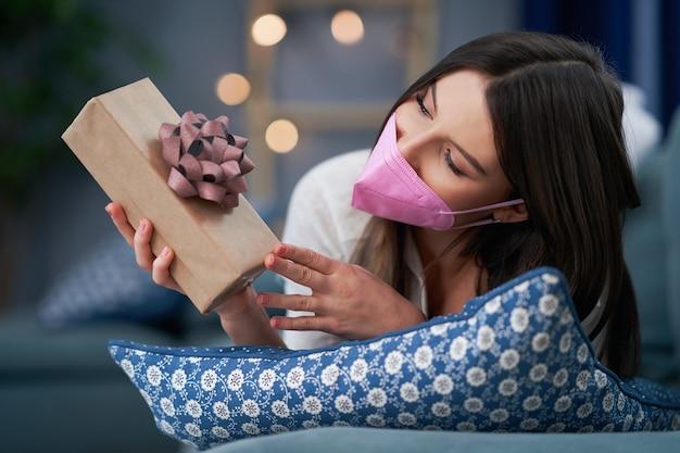 Mulher adulta usando máscara segurando um coração em casa, conceito de dia dos namorados