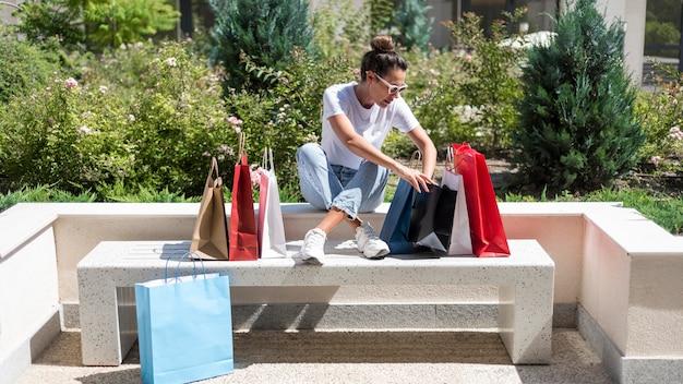 Mulher adulta verificando sacolas de compras