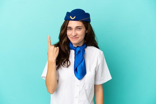 Mulher aeromoça isolada em fundo azul apontando com o dedo indicador uma ótima ideia