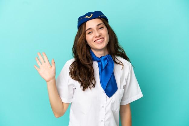 Mulher aeromoça isolada em fundo azul saudando com a mão com expressão feliz