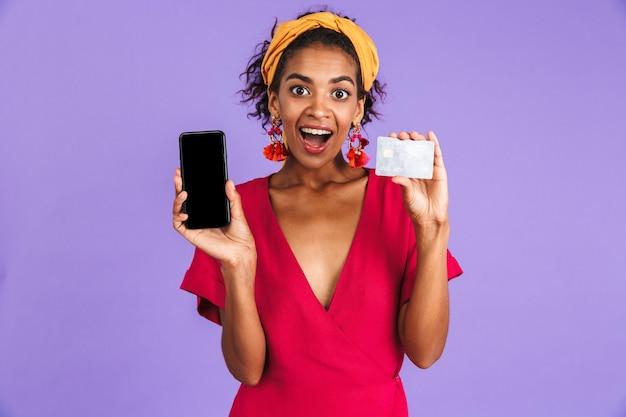 Mulher africana alegre em um vestido segurando um cartão de crédito e mostrando a tela do smartphone em branco