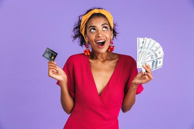 Mulher africana alegre num vestido segurando dinheiro e cartão de crédito enquanto olha por cima da parede roxa
