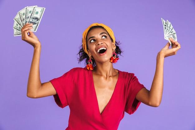 Mulher africana alegre num vestido segurando dinheiro e se divertindo enquanto olha para cima, por cima da parede roxa