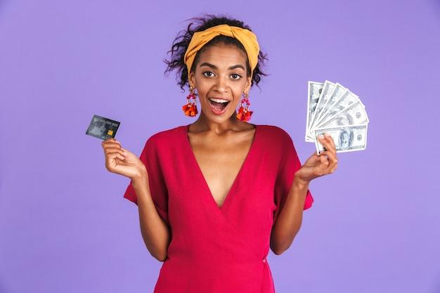 Mulher africana alegre surpresa num vestido segurando dinheiro
