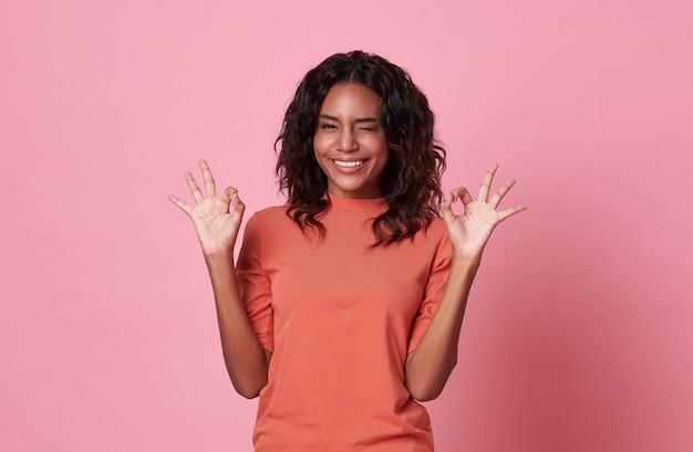 Mulher africana animada mostrando o gesto ok, olhando para a câmera vestindo camiseta laranja casual