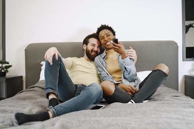 Mulher africana assistindo tv. homem e menina na cama. cara com barba.