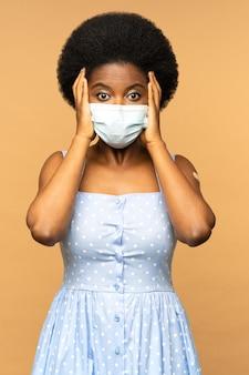 Mulher africana assustada com máscara médica com medo da vacinação e da injeção da vacina contra o coronavírus