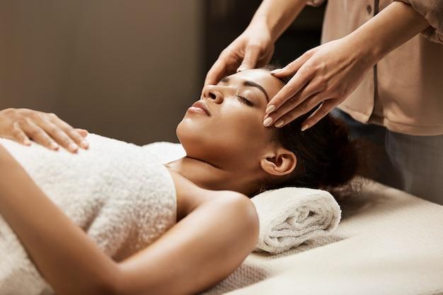 Mulher africana atraente, desfrutando de massagem de rosto no salão spa.