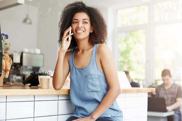 Mulher africana bonita alegre feliz sorrindo falando no telefone, sentado no café.