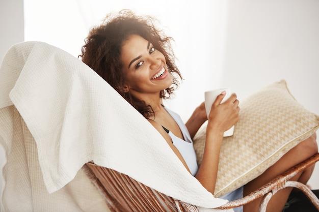 Mulher africana bonita em roupa de noite que sorri guardando o copo que senta-se na cadeira em casa.
