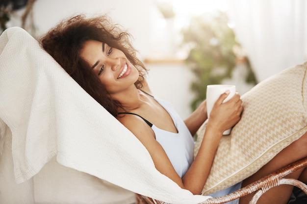 Mulher africana bonita na roupa de noite que sorri guardando o copo que senta o descanso de relaxamento na cadeira em casa.