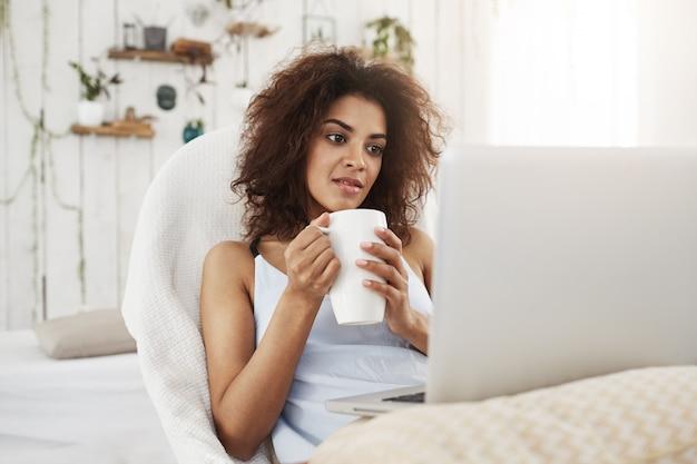 Mulher africana bonita nova na roupa de noite que olha o portátil que guarda o copo que senta-se na cadeira em casa.
