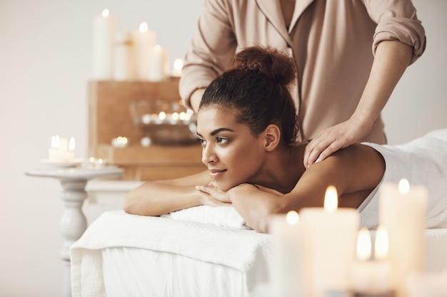 Mulher africana bonita que sorri apreciando a massagem no spa resort.