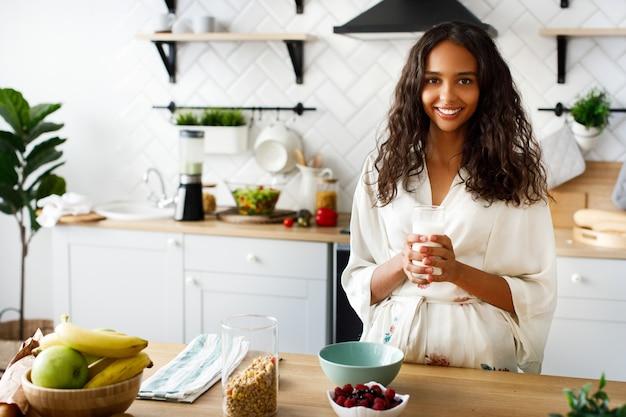 Mulher africana bonita segura um copo com leite e vai fazer um café da manhã