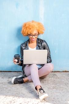 Mulher africana com cabelo encaracolado trabalhando com laptop sentada no fundo da parede azul