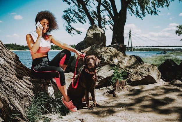Mulher africana com cão falando no telefone.