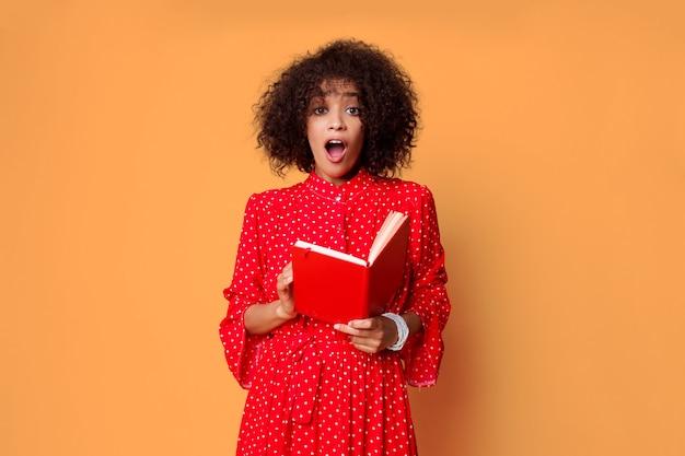 Mulher africana com cara de surpresa, segurando o caderno.