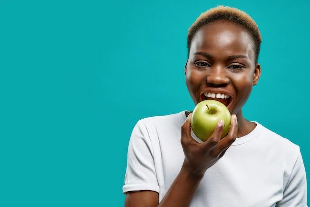 Mulher africana com dentes brancos perfeitos, mordendo a maçã verde.
