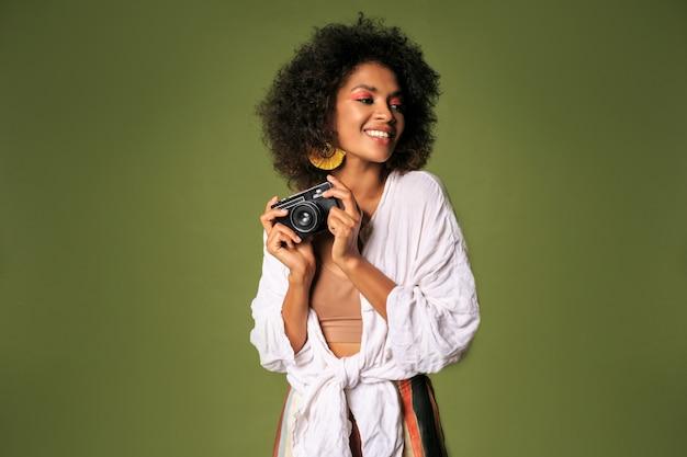 Mulher africana com maquiagem brilhante segurando a câmera fotográfica retrô e rindo.