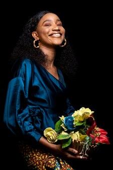 Mulher africana com roupas elegantes segurando um buquê de flores