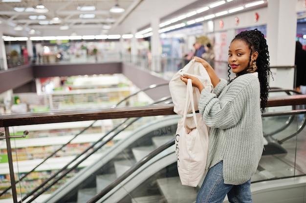 Mulher africana com sacos de compras eco na escada rolante no shopping.
