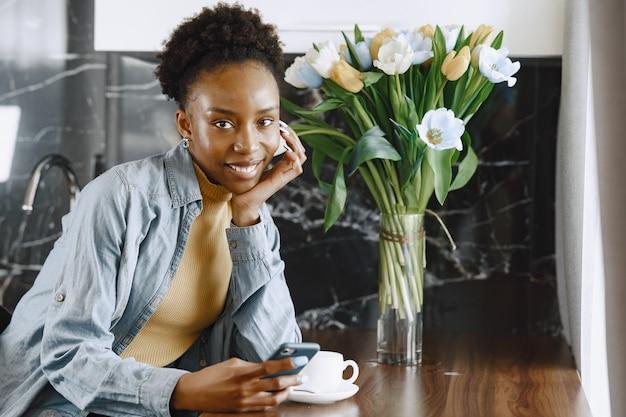 Mulher africana com telefone. garota com cabelo encaracolado. buquê de flores de tulipas.
