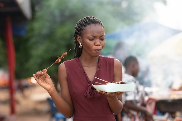 Mulher africana comendo comida de rua