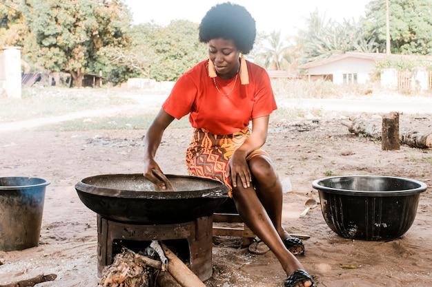Mulher africana completa cozinhando